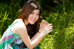 Asian beauty outdoor. Young asian woman basking in the sunlight in the green field Stock Photos