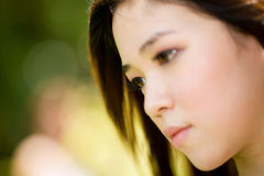 Asian beauty outdoor. Young asian woman face expression in the green field Royalty Free Stock Image