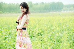 Asian beauty in rape field. Beautiful Asian beauty posing in summer rape field Royalty Free Stock Images