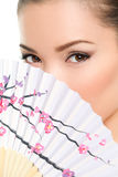 Asian beauty - seductive eyes woman. Chinese or japanese. Eye makeup Asian look with paper fan. Beauty portrait of mixed race Asian / Caucasian female model on Stock Image