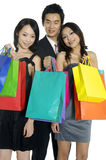 Asian beauty shopping. Photo of three happy friends with shopping bags on the background Royalty Free Stock Photo
