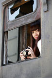 Asian beauty on train. Asian girl holding the camera sitting on an old train caboose Royalty Free Stock Photos