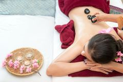 Asian beauty woman lying down on massage bed with traditional hot stones along the spine at Thai spa and wellness center, so relax. And lifestyle.  Healthy Royalty Free Stock Photos