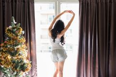 Beauty girl stretch hands in morning. Asian beauty woman waking up in her bed fully rested and stretch extending arm near window and curtain with Christmas tree Stock Image