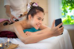 Asian beauty woman lying down on massage bed with traditional hot stones along the spine at Thai spa and wellness center.  She tak. Asian beauty women lying down Royalty Free Stock Image