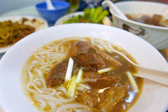 Asian beef soup noodles in white bowl and spoon Royalty Free Stock Photography