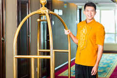 Asian bell boy or porter bringing suitcase to hotel room. Asian Chinese baggage porter or bell boy or page bringing the suitcase of guests with a box van to the stock photos