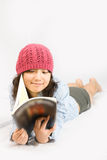 Asian Belle with red hat. A young asian belle with knickers, light blue shirt and pink red hat is reading a magazine royalty free stock photo