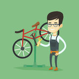 Asian bicycle mechanic working in repair shop. Royalty Free Stock Photos
