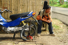 Asian biker roadside breakdown. Royalty Free Stock Photos