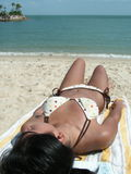 Asian bikini on beach. Resort living with sun tanning. Relaxation at its best.  Asian youth lying down absorbing the sun's nutrition Royalty Free Stock Images