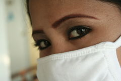 Asian bird flu. An asian girl wearing a mask to prevent asian bird flu Royalty Free Stock Photos
