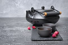 Asian black traditional teapot and teacups with healthy herbal rose tea Royalty Free Stock Photography