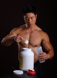 Asian Body Builder pouring a scoop of protein mix Stock Photography