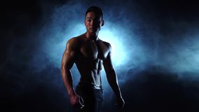 Asian bodybuilder man demonstrates his body, strength and endurance. Black smoke background. Slow motion. Bodybuilder shows his body a pumped up torso and real stock video