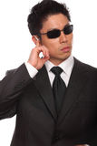 Asian Bodyguard listening to instructions. Wearing a black suite, glasses, and a tie royalty free stock photo