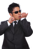 Asian Bodyguard talking in microphone listening. To earpiece stock photos