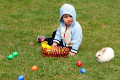 Asian boy. Sitting on the meadow with easter eggs and bunny Stock Photo