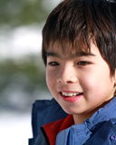 Asian boy. Smiling portrait while playing outside in the snow Royalty Free Stock Photography