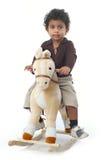 Asian boy. Young Asian Indian boy riding on a felt rocking horse Stock Photos