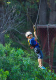 Asian boy adventure. Child happy tree safety rope outdoor extreme activity fun forest royalty free stock photo