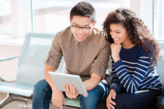 Asian boy and african american girl are using tablet computer. Asian boy in black glasses and african american curly girl girl are using tablet computer Royalty Free Stock Photo