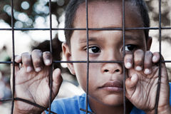 Asian boy against fence with sad expression. Asian boy behind and clinging to fence in the Philippines - contemplating look to the side - shallow depth of field Stock Photo