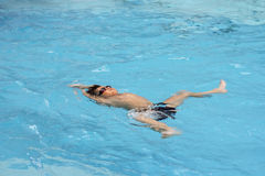 Asian boy back stroke swims in swimming pool Royalty Free Stock Photo