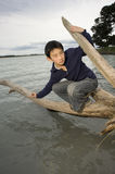 Asian boy balancing on log over water Stock Images