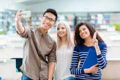 Asian boy, blonde girl and african american woman making selfie Royalty Free Stock Images