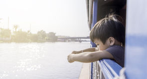 Asian boy on a boat looking out to the river Royalty Free Stock Photo
