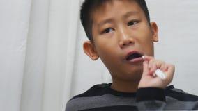 Asian boy brushing his teeth in bathroom stock footage