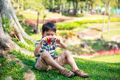Asian boy with camera relaxing outdoors in the day time, travel Stock Photos