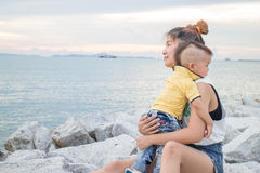 Asian boy chilling with his mother on seaside Royalty Free Stock Images
