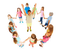 Asian boy in circle of other kids. Cute school age boy with lifted up hands standing in the circle of diverse looking kids Stock Photos