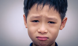 Asian boy crying. Over dark background Royalty Free Stock Photography
