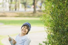 Asian boy with cute smile, wearing a hat, with tablet in hand, standing in garden with lush greenery, online learning concepts royalty free stock photo