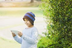 Asian boy with cute, wearing a hat, with looking tablet in hand, standing in garden with lush greenery, online learning concepts stock images