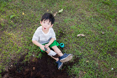 Asian  boy digging in the garden Stock Images