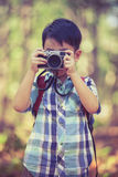 Asian boy with digital camera in beautiful outdoor. Retro style. stock photos
