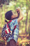 Asian boy with digital camera in beautiful outdoor. Retro style. Stock Photography