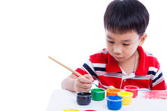Asian boy draw image using drawing instruments. Little asian (thai) boy draw image using multicolored drawing instruments (watercolor paints, paintbrush) Royalty Free Stock Photos