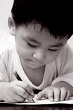 Asian boy drawing on paper. Asian boy is holding a pencil and writing/drawing on a white paper Stock Photo