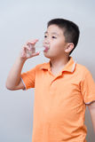 Asian boy drinking water from glass Royalty Free Stock Photos