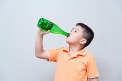 Asian boy drinking water from green bottle stock images