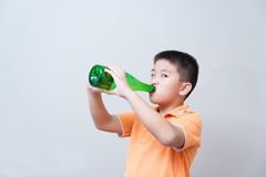 Asian boy drinking water from green bottle stock photo