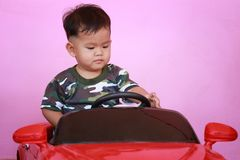 Asian boy driving a toy car. Asian boy driving a toy car and have pink wall background Royalty Free Stock Images