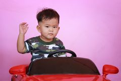 Asian boy driving a toy car. Asian boy driving a toy car and have pink wall background Stock Photography