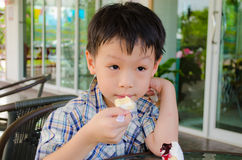 Asian boy eating cake Royalty Free Stock Photo