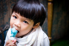 Asian boy is eating candy Royalty Free Stock Photos